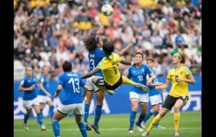 Jamaica's Khadija Shaw (airborne) attempts an acrobatic shot that was contested by Italy's team captain Sara Gama (3)  during their FIFA Women's World Cup group stage match on June 14, 2019. Jamaica's Havana Solaun (right) and Italy's Elisa Bartoli (13) look on.
