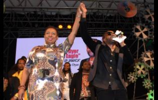 Entertainment and Culture Minister Olivia Grange (left) holds aloft the hand of Loaded Eagle, the 2019 Festival Song Competition winner.