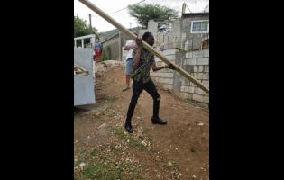 Bounty Killer picks up a piece of lumber that was among the building supplies donated.