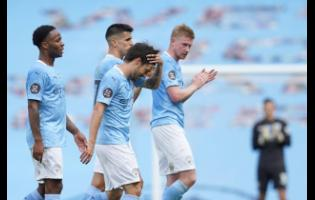 Manchester City's David Silva is applauded by teammates at the end of the English Premier League  match against Norwich City at the Etihad Stadium in Manchester, England, on Sunday, July 26.
