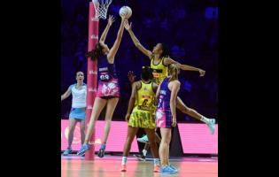 Jamaica goalkeeper Shamera Sterling (second right) goes high to defend ahead of Scotland goal shooter Emma Barrie (left), while Jamaica's Adean Thomas (second left) and Lynsey Gallagher(GA) look on during their Vitaly Netball World Cup Group G game at the M&S Bank Arena in Liverpool, England, on July 17, 2019.