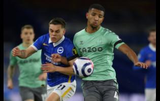 Brighton's Leandro Trossard, left, fights for the ball with Everton's Mason Holgate during the English Premier League soccer match between Brighton and Everton at the Falmer Stadium in Brighton, England, yesterday.