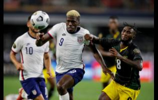 United States forward Gyasi Zardes (9) powering his way past Jamaica's Oniel Fisher (8)  in the second half of last night's Concacaf Gold Cup quarter-final  in Arlington, Texas. United States won 1-0.