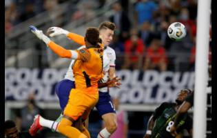 United States' forward Matthew Hoppe (centre) heads the ball past Jamaica's goalkeeper Andre Blake (left) to score last night's winning goal in their Concacaf Gold Cup quarter-final match played at the AT&T Stadium in Arlington, Texas.