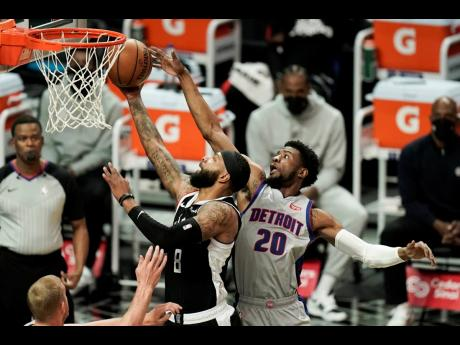 Los Angeles Clippers' Marcus Morris Sr (left) shoots under the defence from Detroit Pistons' Josh Jackson during the first half of an NBA basketball game on Sunday, April 11, in Los Angeles.