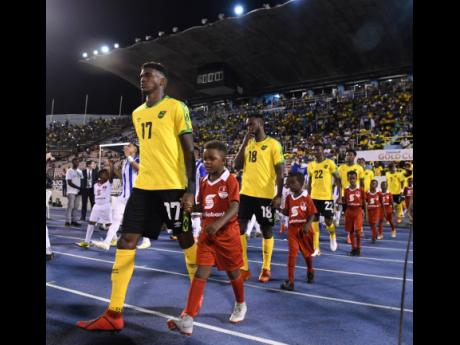Damion Lowe (left) leads the Reggae Boyz on to the field at the National Stadium to take on Honduras in a Concacaf Gold Cup match on Monday, June 17, 2019.
