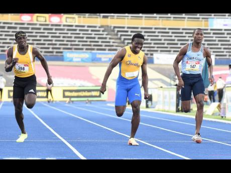 St Elizabeth Technical High School's Sachin Dennis (centre) strides to victory ahead of Petersfield High School's Antonio Watson (left) and Edwin Allen's Bryan Levell in the Class One Boys 100m final at the ISSA/GraceKennedy Boys and Girls' Athletics Championships at the National Stadium on Thursday.