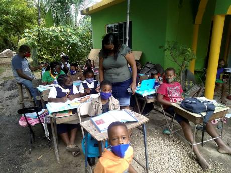 In this November 2020 photo, Garnet Foster and his wife, Camille, are seen helping children in Bullet Tree, Westmoreland, with schoolwork.