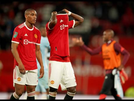Manchester United's Anthony Martial (left) and Eric Bailly leave the pitch at the end of the English League Cup soccer match against West Ham at Old Trafford in Manchester, England, yesterday. West Ham won the match 1-0.